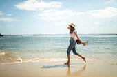 Young barefoot woman wearing jeans, t-shirt and sun hat, holding slippers and running at seashore during beautiful day in Lisbon