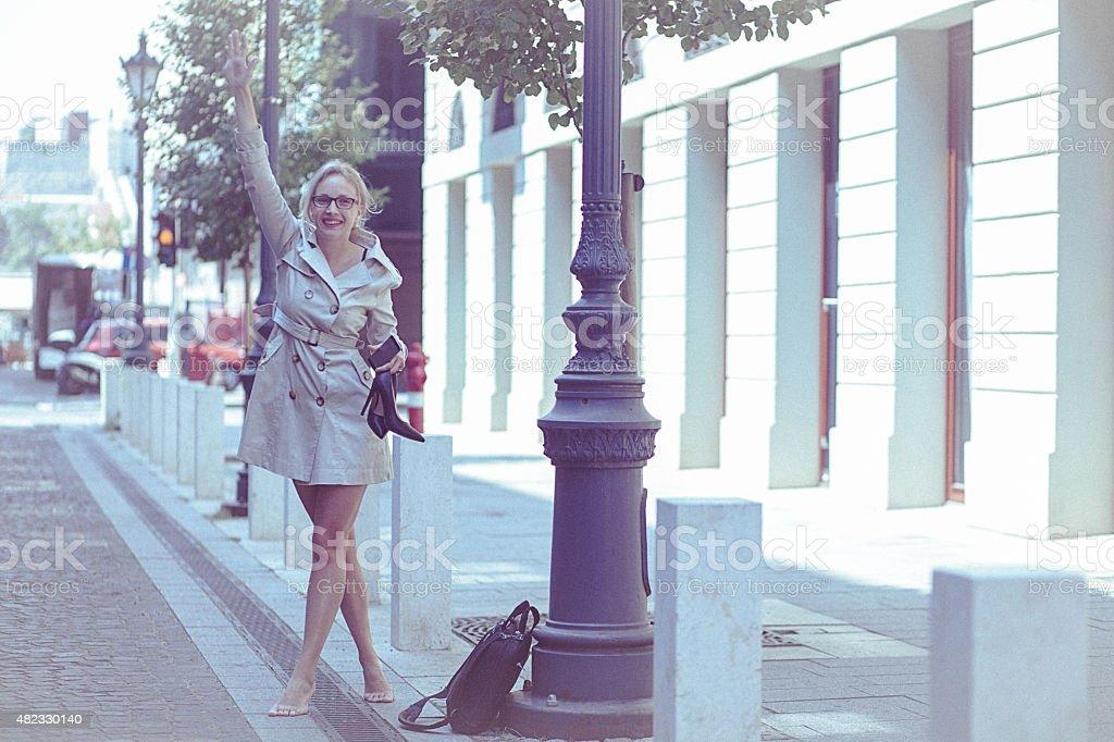 Молодые босиком женщина shouts на такси on the city street стоковое фото