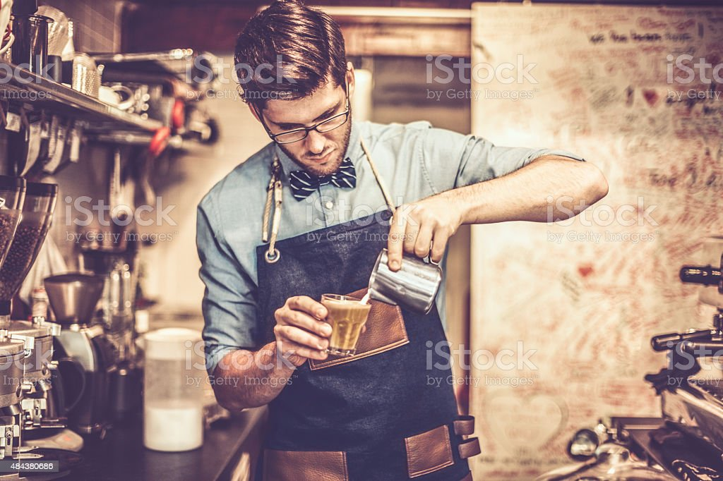 Young barista is making a coffee Young barista is making a coffee  2015 Stock Photo