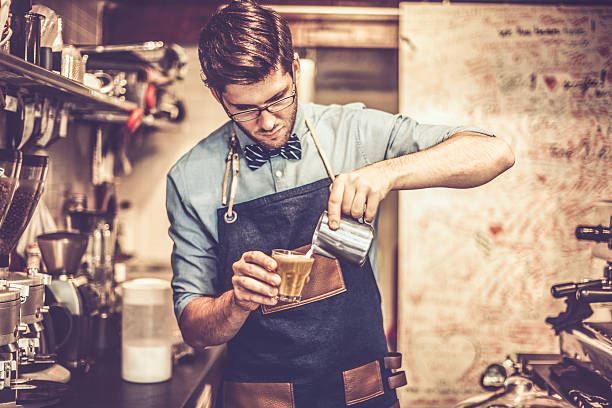 young barista is making a coffee - barista stock photos and pictures