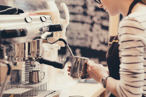 young barista is preparing coffee - barista making coffee stock pictures, royalty-free photos & images