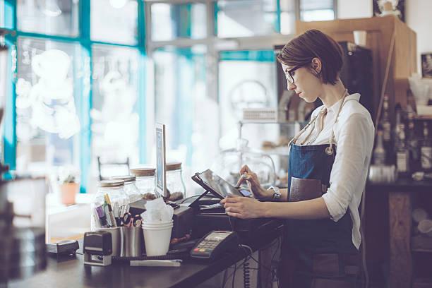 junge barista arbeitet in einem café - kaffee shop stock-fotos und bilder