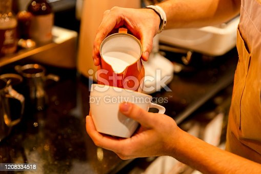 Portrait of young handsome male barista making a cup of coffee and pouring latte art with milk inside of his cafe shop