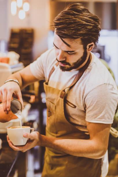 jungen barista gießen latte art - italienische lebensart stock-fotos und bilder