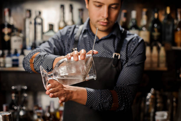 junge barkeeper gießen kaltes alkoholisches getränk aus einem großen glas - dekorierte schnapsflaschen stock-fotos und bilder