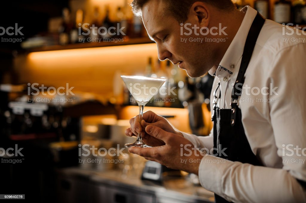 Young barman with closed eyes holding a glass of fresh alcoholic cocktail stock photo