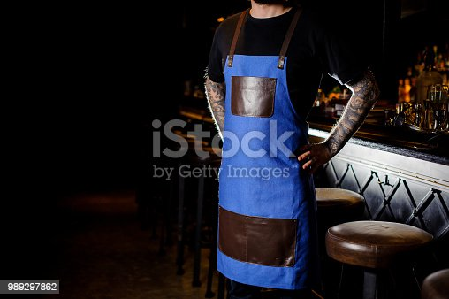 1003493404istockphoto Young barman with tattoo on hands dressed in blue and brown apron 989297862