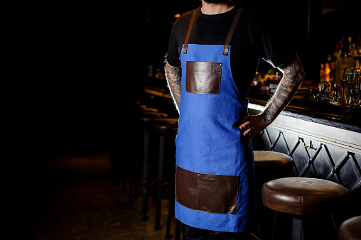 1003493404 istock photo Young barman with tattoo on hands dressed in blue and brown apron 989297862
