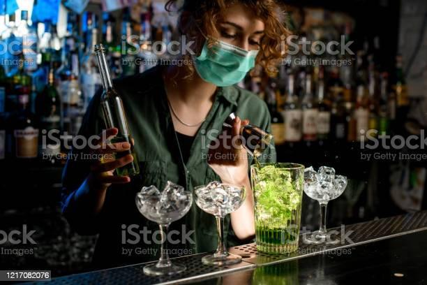 Young bartender girl in a medical mask pour green liquid from beaker picture id1217082076?b=1&k=6&m=1217082076&s=612x612&h=kkovi8zyxl9cs mh07vu 96 xbcrus d xd4jdhgig8=