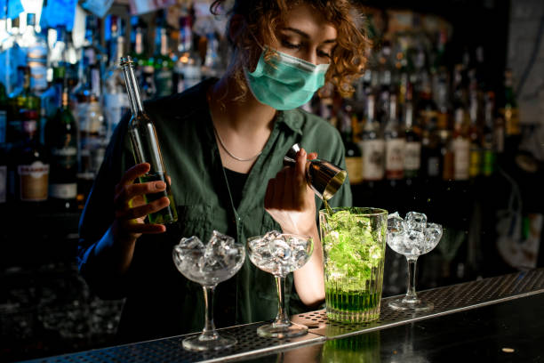 Young bartender girl in a medical mask pour green liquid from beaker into glass with ice. Young bartender girl in a medical mask pour green liquid from beaker into glass with ice. Medical mask for prophylaxis and protection from coronavirus COVID-19. bartender stock pictures, royalty-free photos & images