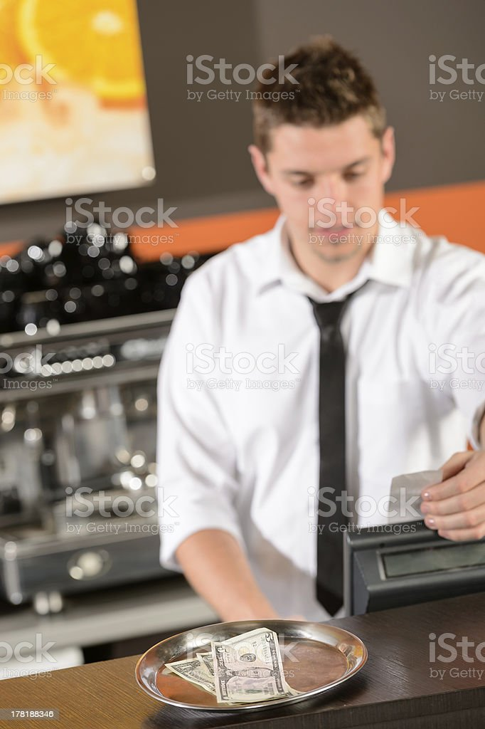 Young bartender in uniform taking cash dollar royalty-free stock photo