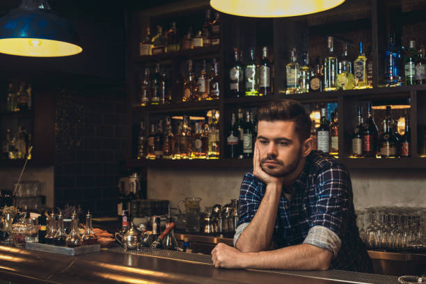 Young bartender leaning on bar counter thoughtful stock photo
