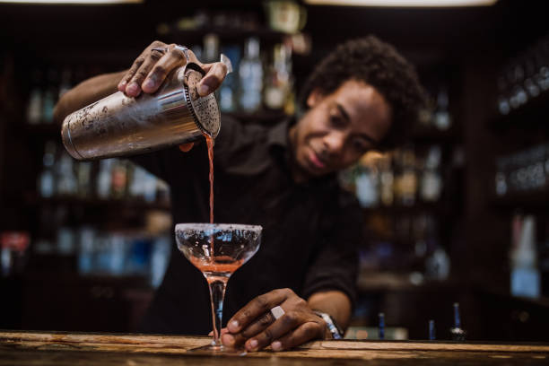 Young bartender pouring cocktails in a cocktail bar Barman is making cocktail at night club cocktail shaker stock pictures, royalty-free photos & images