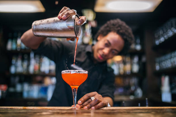 jeune barman versant des cocktails dans un bar à cocktails - barman photos et images de collection