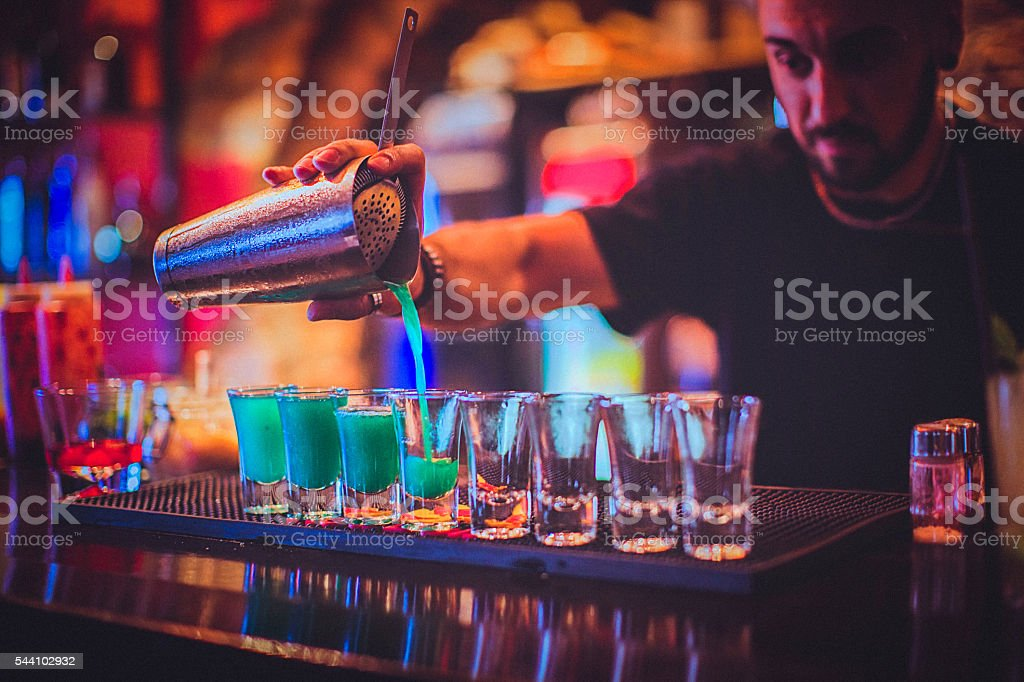 Young bartender pouring cocktails in a nightlife bar stock photo