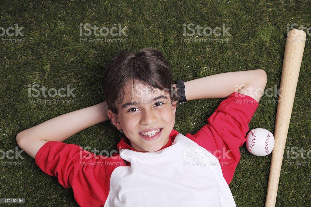 Young baseball player lying on grass stock photo