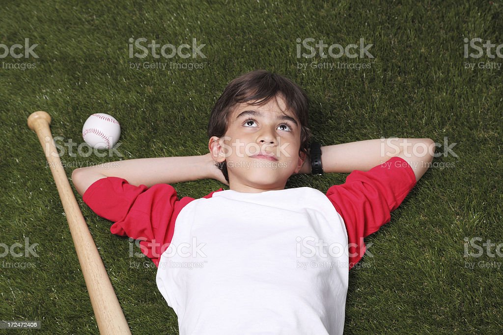 Young baseball player lying on grass royalty-free stock photo