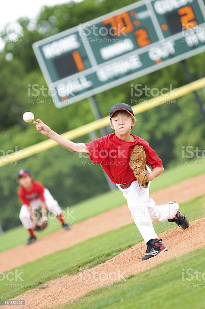 Young baseball player pitching the ball stock photo