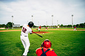 Rear viewpoint of Hispanic baseball player standing in batter's box and swinging his bat at thrown pitch.