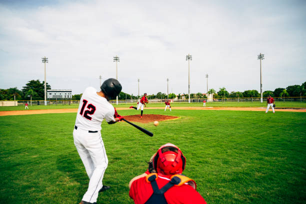 Young baseball player swinging his bat at thrown pitch Rear viewpoint of Hispanic baseball player standing in batter's box and swinging his bat at thrown pitch. baseball sport stock pictures, royalty-free photos & images