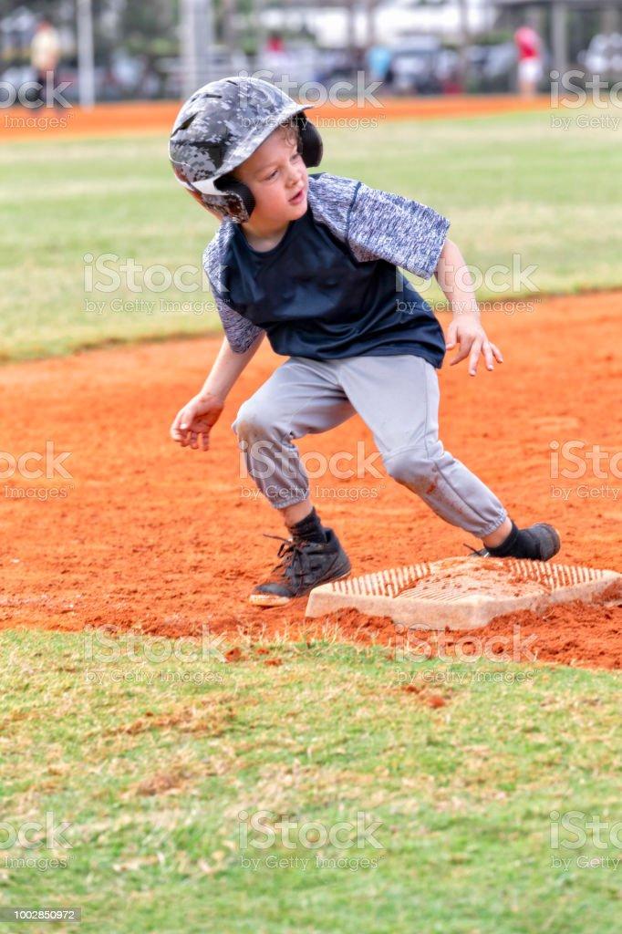Young baseball player tags third base during a baseball game stock photo