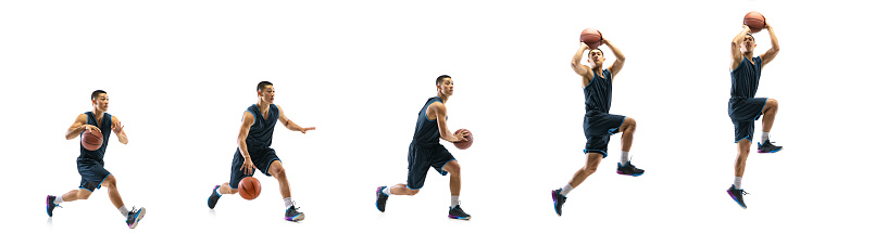 Young basketball player against white studio background in motion of step-to-step goal