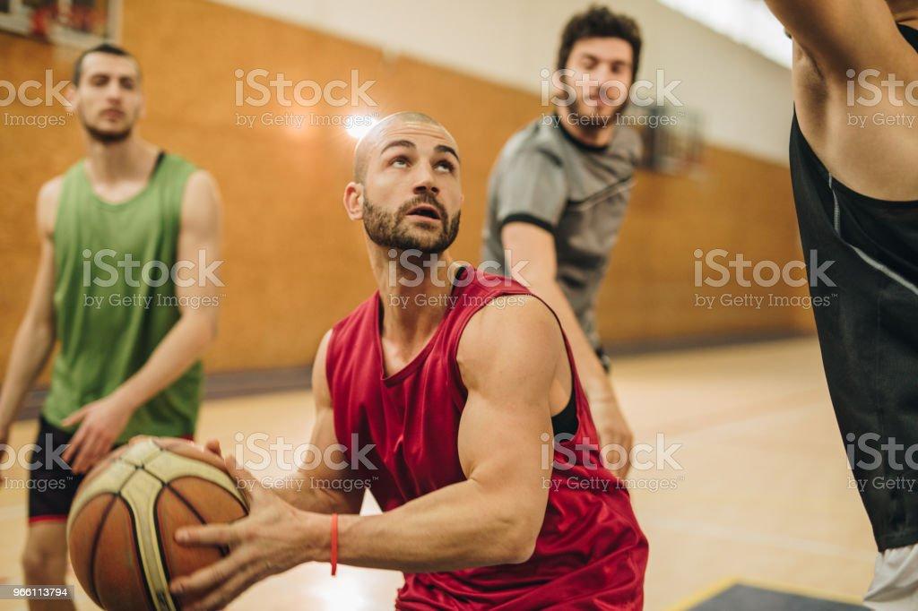 Jonge basketbalspeler dribbelen van zijn tegenstanders tijdens het spel. - Royalty-free Aanvallen - Sporten Stockfoto
