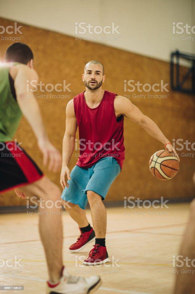 Jugador de baloncesto jóvenes metiéndose en el delito durante el partido. - Foto de stock de Actividades recreativas libre de derechos