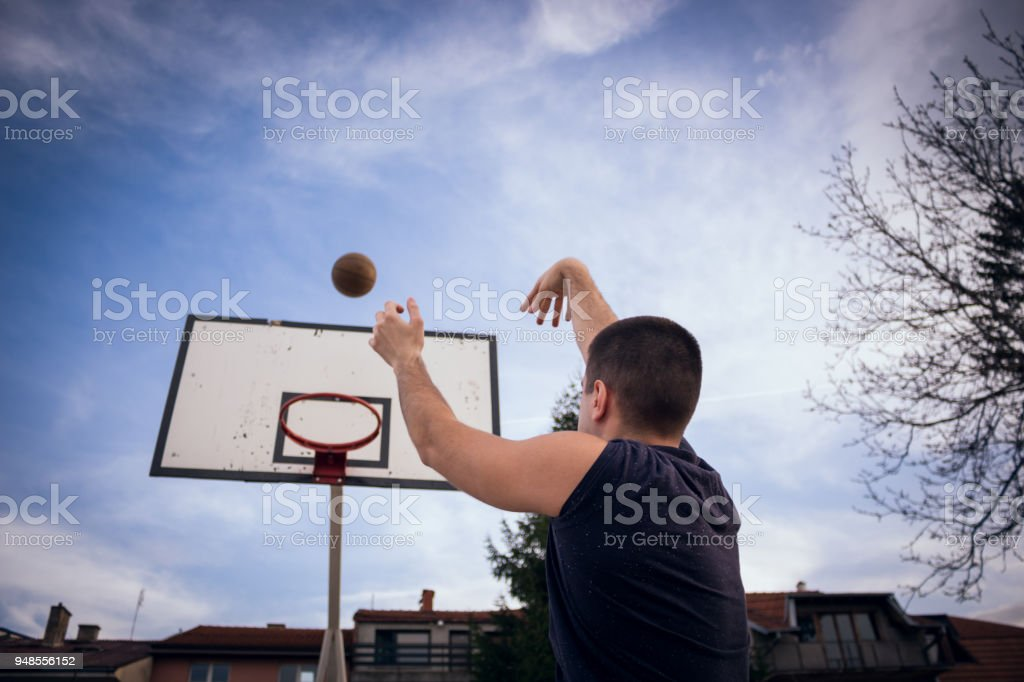 Young basketball player is holding ball stock photo