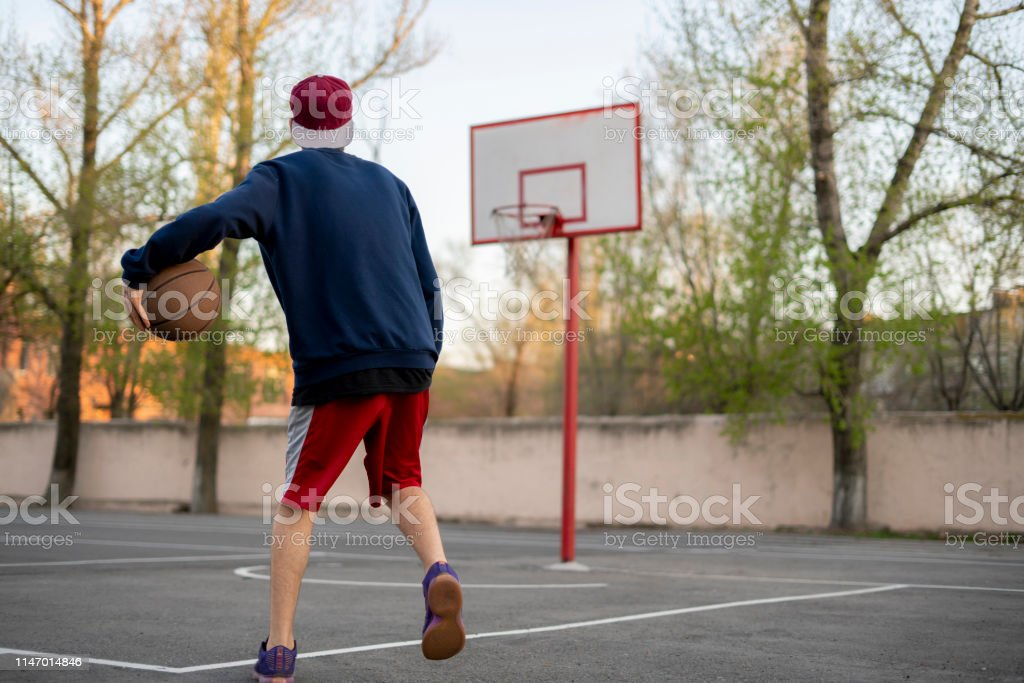 young basketball player training practice to dribble outdoor on the...