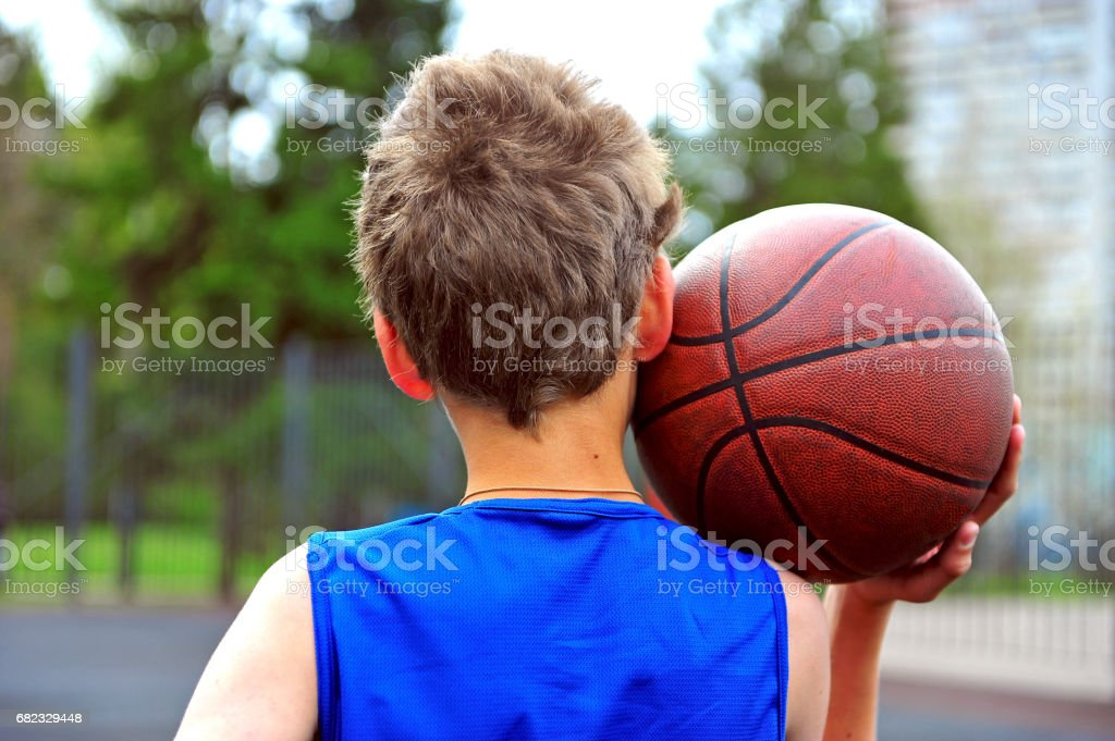 Young basketball player with a ball on his shoulder on the court stock photo
