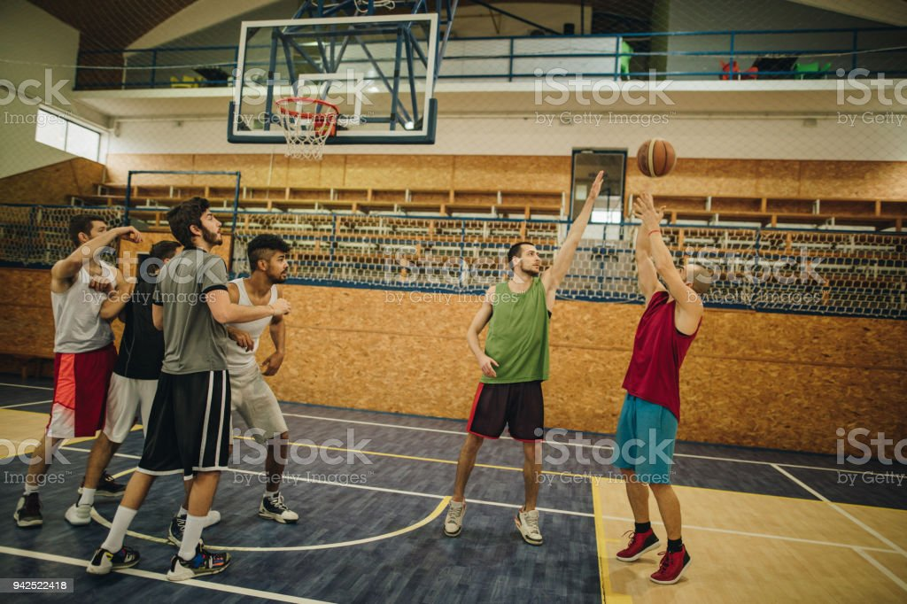 Large group of young athletic men playing basketball.