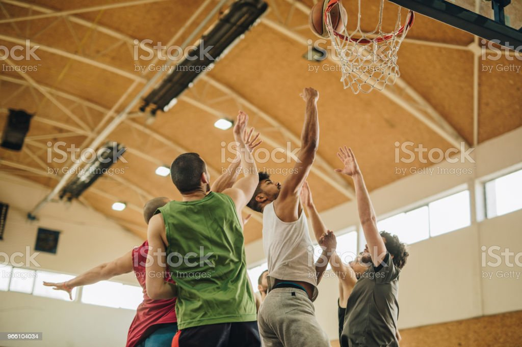 Young basketball players during sport match in school gymnasium. - Royalty-free Adult Stock Photo