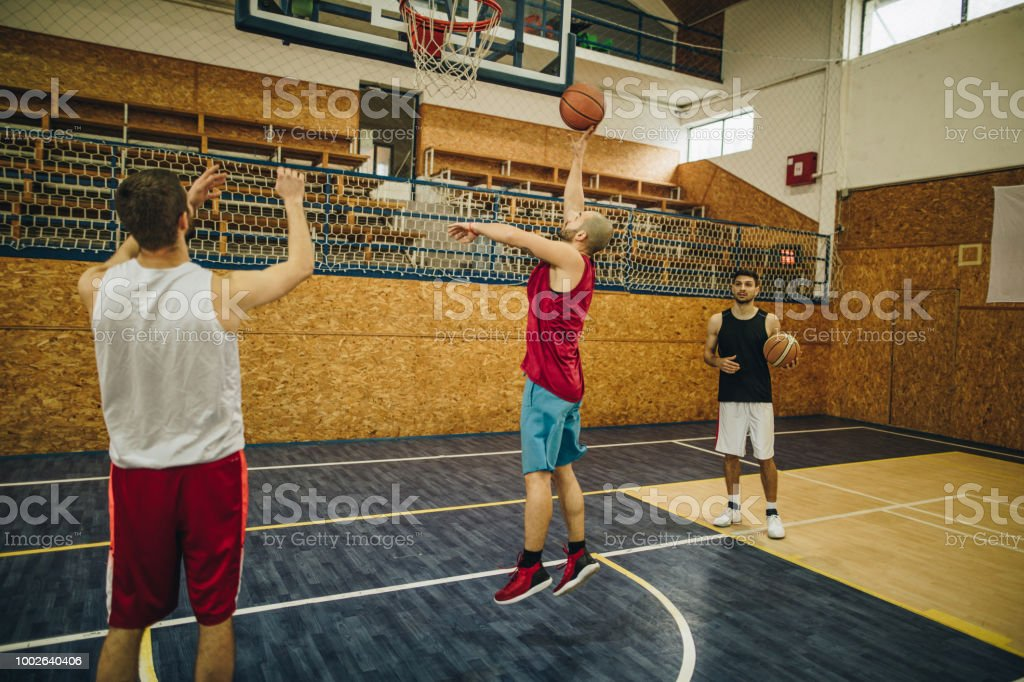 Small group of athletes having a basketball training on the court.
