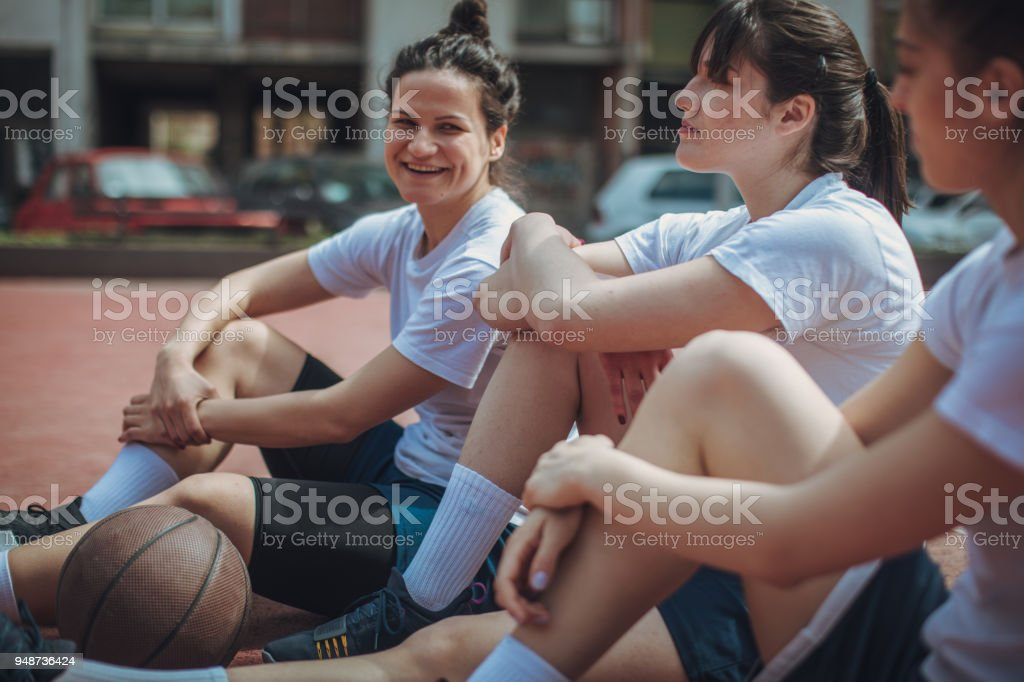 Young basketball players sitting on the court stock photo