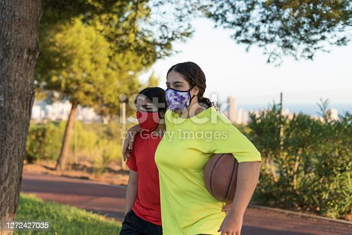 young basketball players walking out of the court with protective face mask.