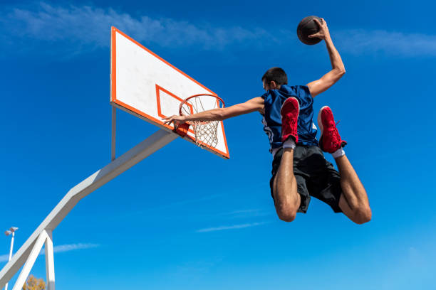 Young Basketball street player making slam dunk Young Basketball street player making slam dunk. slam dunk stock pictures, royalty-free photos & images