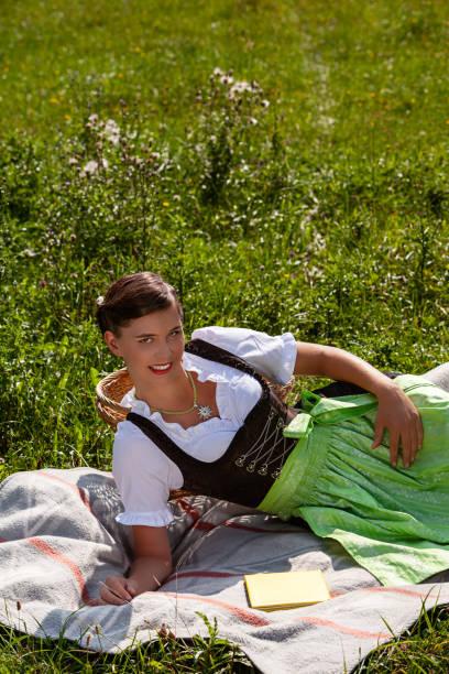 junge bayerische frau im dirndl - bayerische brotzeit stock-fotos und bilder