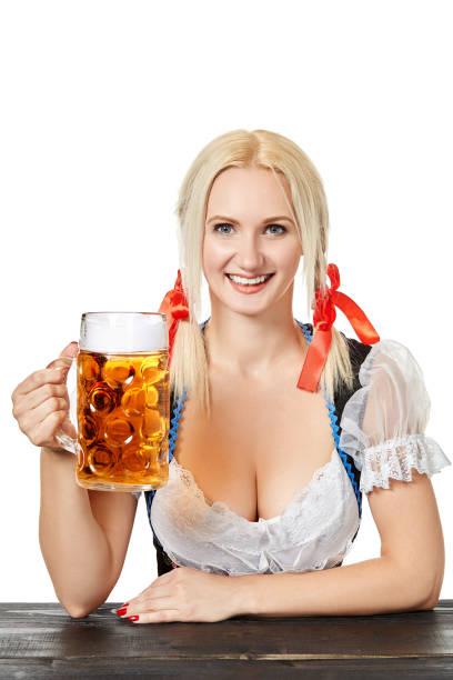 junge bayerische frau im dirndl sitzen am tisch mit bier auf weißem hintergrund - bavaria porzellan stock-fotos und bilder