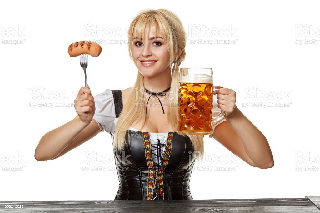 Junge bayerische Frau im Dirndl sitzen am Tisch mit Bier auf weißem Hintergrund – Foto