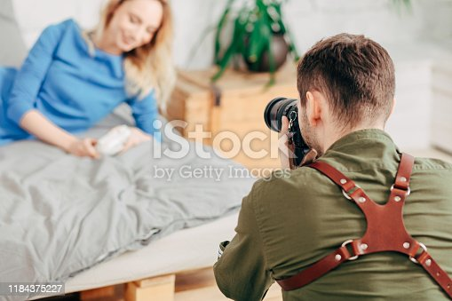 young beaded man working with a model, close up back view photo. blurred background