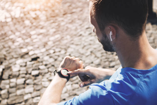 Young bearded athlete with bluetooth headphones analyzes result of training on smartwatch. Concept of modern athlete with smart watch and gadgets in urban environment stock photo