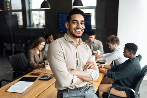 Successful Person. Portrait of confident smiling bearded businessman sitting leaning on desk in office, posing with folded arms and looking at camera, colleagues working in blurred background