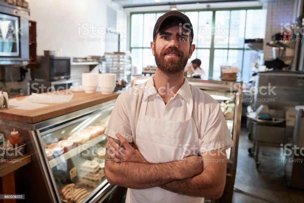 Jeune barbu souriant à la caméra dans sa boutique de boucher - Photo