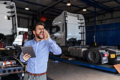 istock Young bearded chief of export department standing in garage, holding tablet and calling his employee. In background are trucks. 1285071655