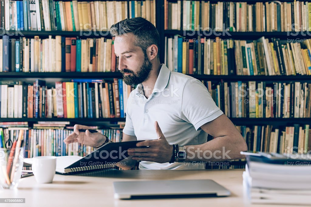 young bearded creative working at desk stock photo
