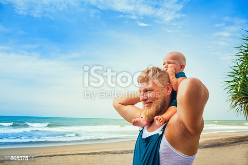 Happy family - young bearded hipster man, funny baby son walk together by tropical beach along sea surf. Little child sit on fathers shoulders and have fun. Travel lifestyle, summer vacation with kids