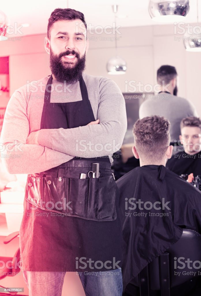 Young bearded guy displaying his workplace at hairdressing salon stock photo