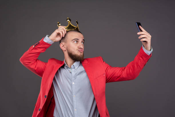 young bearded handsome man in gold crown taking selfie looking at smartphone - arrogance stock pictures, royalty-free photos & images