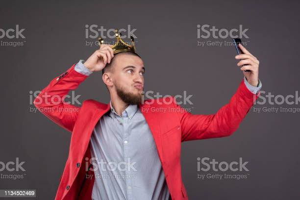 Photo of Young bearded handsome man in gold crown taking selfie looking at smartphone